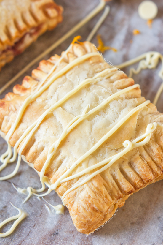 Cranberry and Orange Hand Pies - Festive hand pies filled with cranberry and orange and drizzled with white chocolate.